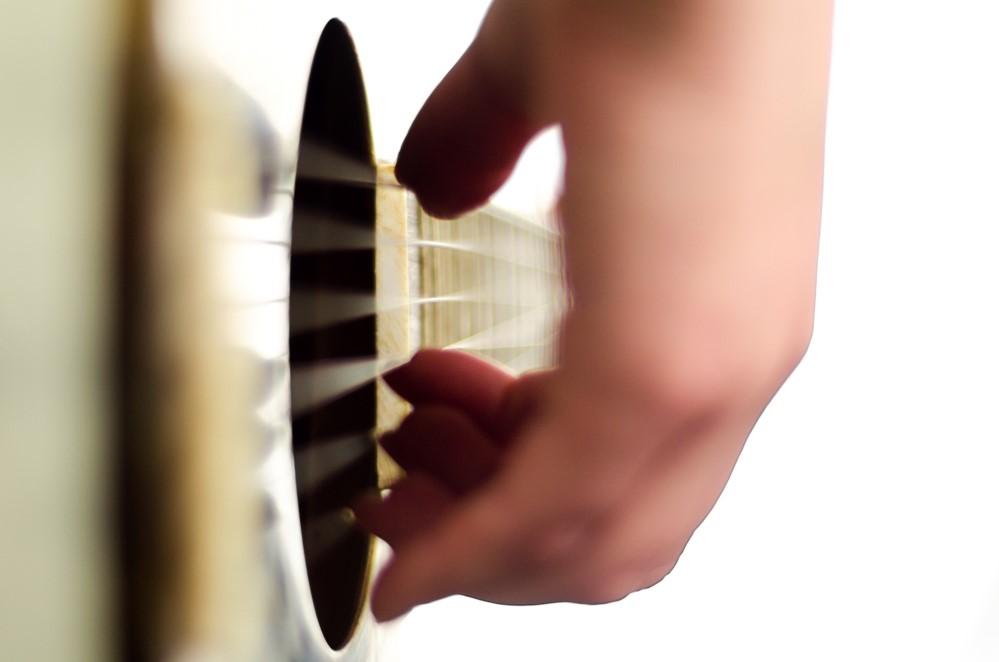 Играет перебором на гитаре