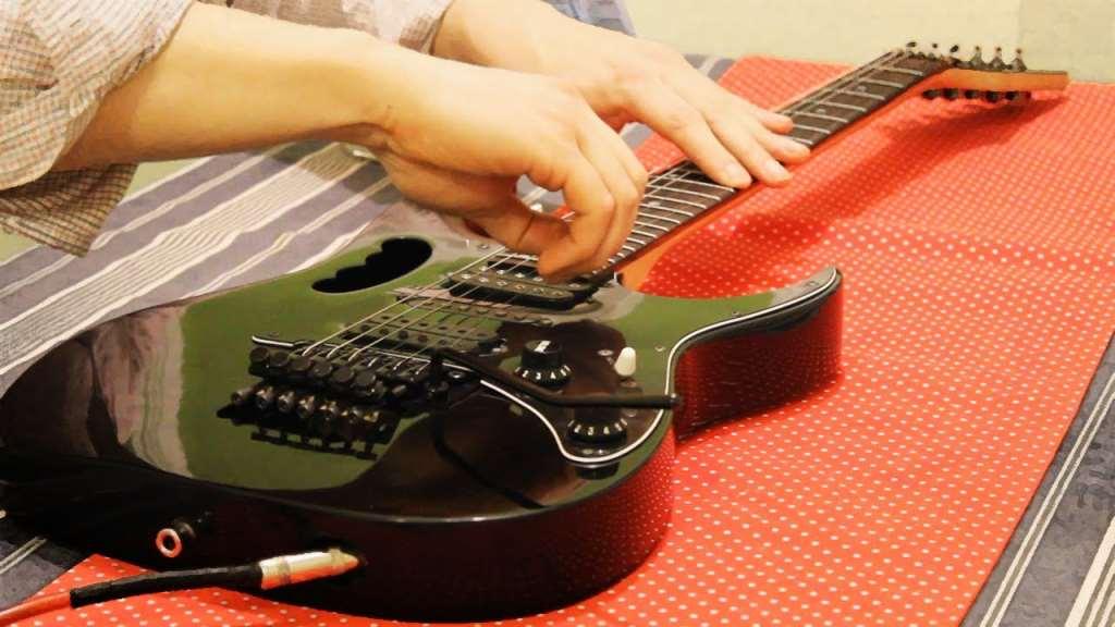 человек меняет струны на электрогитаре