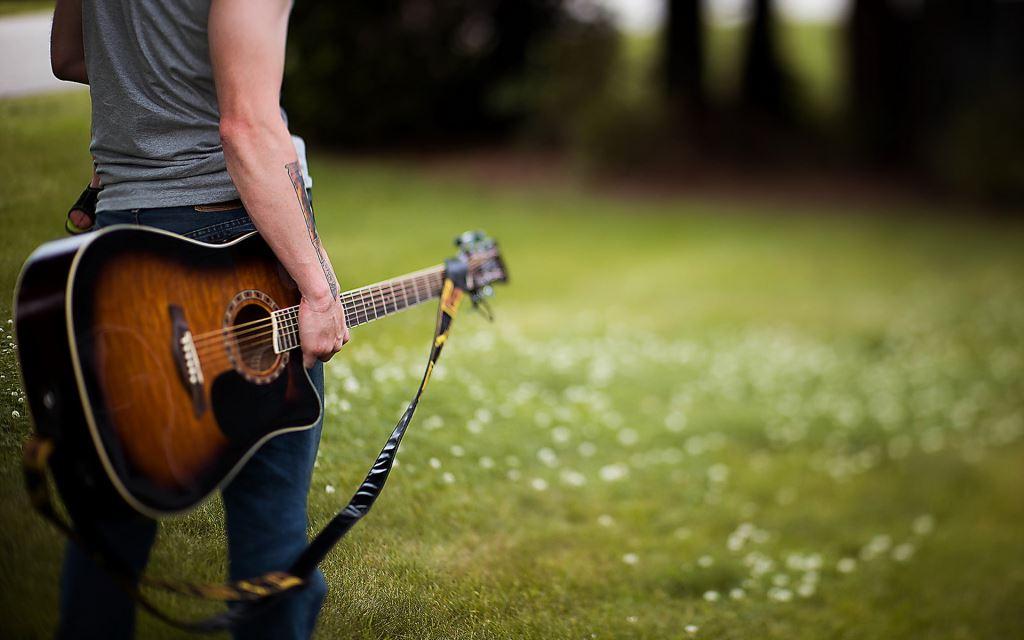 Парень с гитарой на зеленом лугу